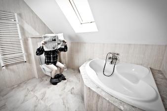 El hombre está sentado en el inodoro.