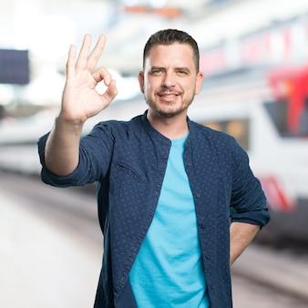 El hombre joven que llevaba un traje azul. Haciendo un gesto bien.