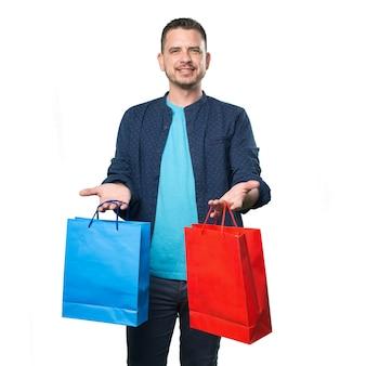 El hombre joven que llevaba un traje azul. La celebración de bolsas de la compra.
