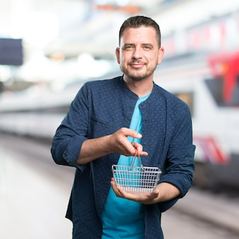 El hombre joven que llevaba un traje azul. La celebración de una cesta de la compra.