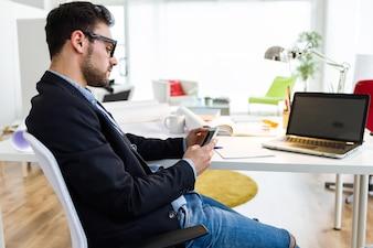 El hombre sentado en la mesa y el uso de teléfonos inteligentes