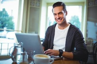 El hombre usando la computadora portátil mientras que el café en la cafetería © sonriendo