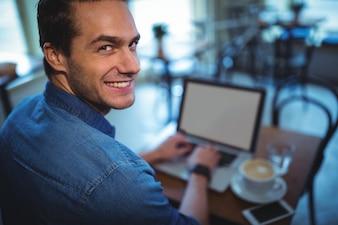 El hombre usando la computadora portátil mientras que el café en la cafetería ©