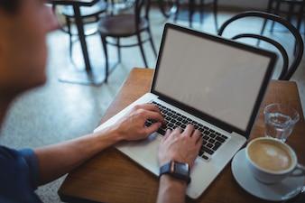 El hombre usando la computadora portátil mientras que el café