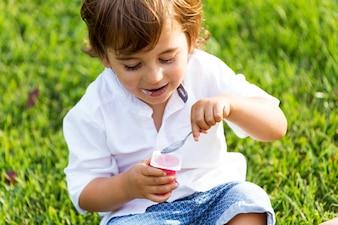 El niño comiendo yogur en el parque.