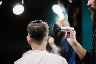 El peluquero cubre la cabeza del hombre con el polvo