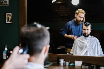 El peluquero hace el corte del descoloramiento en el pelo del hombre