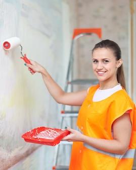 El pintor pinta la pared con el rodillo