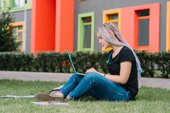Elegante colegiala en el parque con la computadora portátil