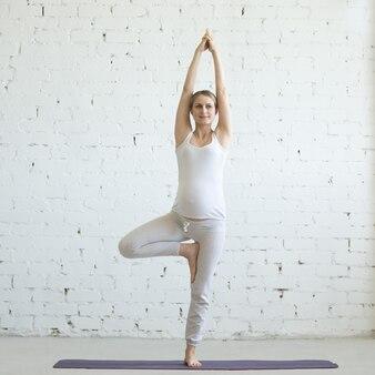 Embarazada joven haciendo yoga prenatal. Vrksasana pose