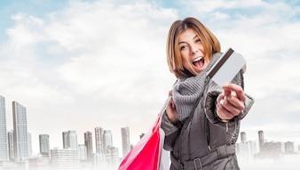 Empleada feliz con bolsas de la compra y tarjeta de crédito