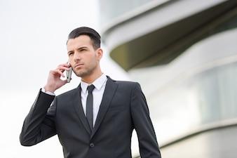 Empleado serio usando su teléfono móvil