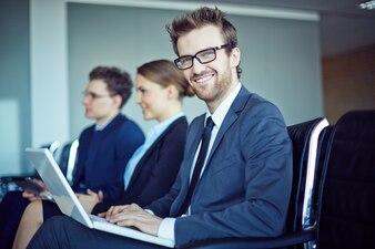 Empleado sonriente con corbata y portátil