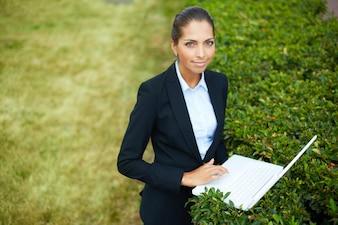 Empresaria con el portátil sobre un arbusto