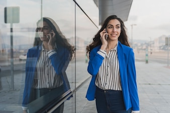 Empresaria joven elegante hablando por teléfono