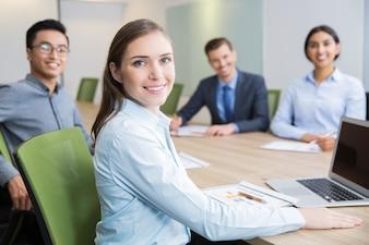Empresaria joven sonriente sentado en la sala de juntas