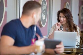 Empresaria joven sonriente trabajando con su portátil