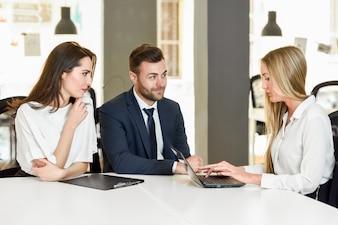 Empresaria rubia explicando con portátil a sonriente joven cou