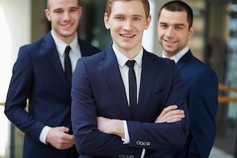 Empresario de pie delante de sus compañeros de trabajo