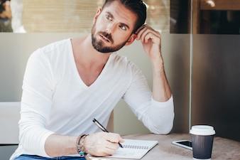 Empresario inteligente pensando mientras escribe en el bloc de notas en el café acera