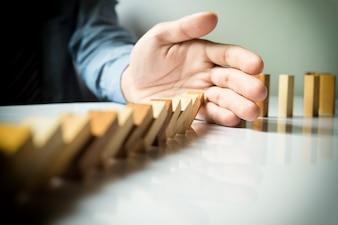 Empresario mano parada dominó continua derribado o riesgo con copyspace