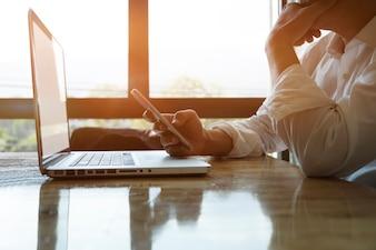 Empresario reflexivo o empresario experimentado utilizando smartphone y portátil para analizar la información