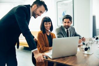 Empresarios sonrientes trabajando con el portátil