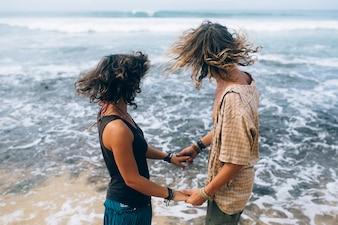 Enamorados cogiéndose las manos y mirando al mar