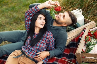 Encantadora pareja de jóvenes divirtiéndose en la hierba