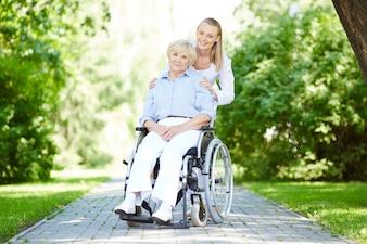 Enfermera caminando con la paciente mayor en silla de ruedas