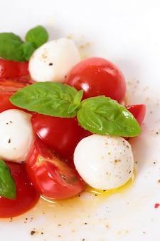 Ensalada caprese con mozzarella, aceite de oliva y hojas de albahaca
