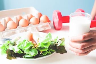 Ensalada fresca con huevo y mano sosteniendo el vaso de leche, menú saludable con pesas rojas, concepto de estilo de vida saludable