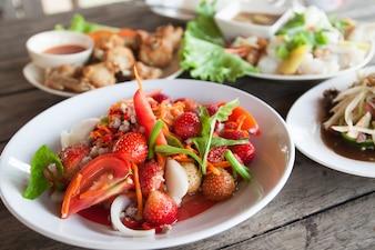 Ensalada picante de fresa en plato blanco, menú Spacial en Tailandia