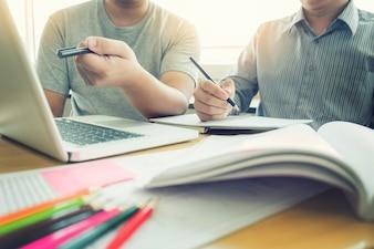 Enseñar el concepto de tecnología de ayuda. Mujer joven profesor o tutor con los estudiantes adultos en el aula en el escritorio con papeles, ordenador portátil. Estudios curso