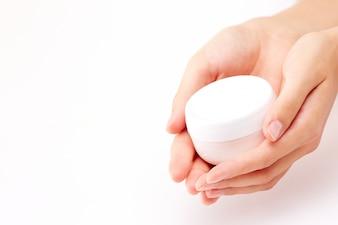 Envase de crema en manos de una mujer