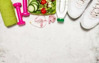 Equipo deportivo con fruta y agua sobre una superficie blanca