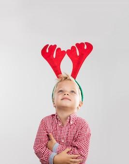Escena de navidad de niño feliz con cuernos de reno