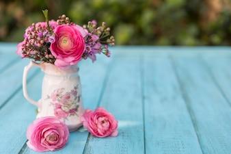 Escena de primavera con jarrón y flores en tonos rosas