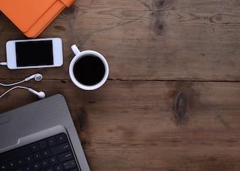 Escritorio con libreta smartphone café y portátil