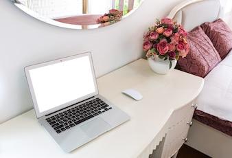 Escritorio con portátil y flores