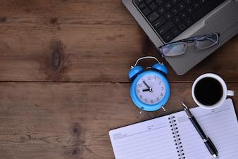 Espacio de trabajo con libreta reloj café y portátil