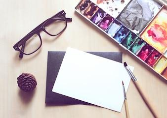 Espacio de trabajo de artista con pincel y pintura en la tarjeta en blanco, efecto de filtro retro