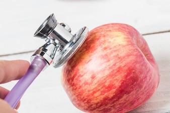 Estetoscopio médico y una manzana sobre fondo de madera. Imagen de concepto de estilo de vida saludable.