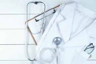 Estetoscopio, sujetapapeles y uniforme médico en blanco escritorio de madera