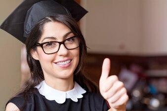Estudiante alegre mostrando el pulgar hacia arriba