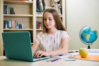 Estudiante concentrado usando la computadora portátil en el escritorio