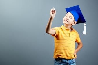 Estudiante de primaria con un gorro de graduación y una tiza