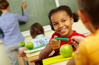 Estudiante feliz compartiendo su lápiz verde