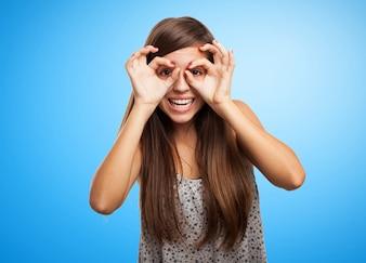 Estudiante juguetona con el gesto de las gafas sobre fondo azul
