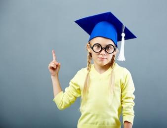 Estudiante señalando hacia arriba con gorro de graduación